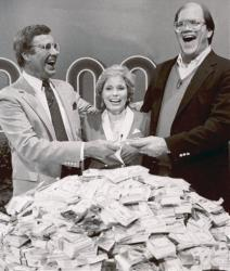 This Jan. 16, 1986, photo shows host Jim Lange, left, congratulating Connie and Steve Rutenbar of Mission Viejo, Calif., after they won $1 million on the TV show The $1,000,000 Chance of a Lifetime.