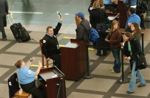 An identification security screener with hand raised calls for a TSA screener at Denver International Airport on Wednesday, Nov. 21, 2007 in Denver, Colo.