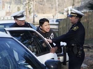 Cincinnati police remove a witness after authorities say Sammy Lorenz, 8, was shot and killed while playing with a gun in Cincinnati, Saturday, March 1, 2014.