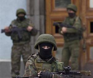 Unidentified armed men guard the entrance to the local government building in downtown Simferopol, Ukraine, yesterday.