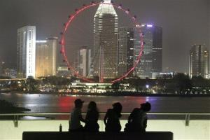 People are silhouetted against the backdrop of Singapore's financial skyline and the Singapore Flyer Ferris wheel.