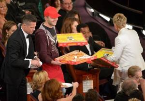 Brad Pitt, left, and Ellen DeGeneres, right, pass out pizza in the audience during the Oscars at the Dolby Theatre on Sunday, March 2, 2014, in Los Angeles.