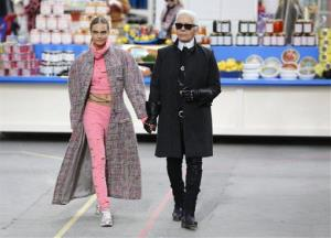 Model Cara Delevingne holds the hand of  German fashion designer Karl Lagerfeld waves after the presentation of Chanel's ready to wear fall/winter 2014-2015 fashion collection presented in Paris, Tuesday, March 4, 2014.