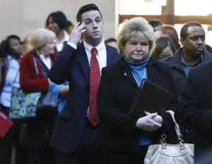 In this Wednesday, Jan. 22, 2014 photo, job seekers line up to meet prospective employers during a career fair at a hotel in Dallas.