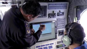 Malaysian maritime official Mohd Amdan Kurish, left, checks radar in the search for the missing Malaysia Airlines plane off Kelantan, Malaysia, Sunday, March 9, 2014.