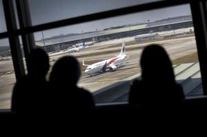 Women are silhouetted as they watch a Malaysia Airlines jet taxi on the tarmac at the Kuala Lumpur International Airport Tuesday.