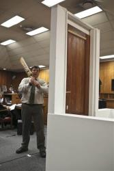 Forensic investigator Johannes Vermeulen, with a cricket bat in hand, demonstrates on a mock-up toilet and door details of how the door could have been broken down.