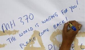 A woman writes a message for passengers aboard a missing Malaysia Airlines plane on a banner at Kuala Lumpur International Airport.