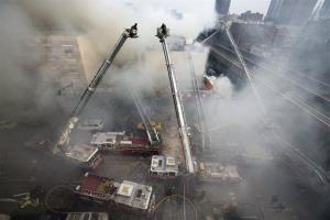 Firefighters respond to an explosion that leveled two apartment buildings in the East Harlem neighborhood of New York, Wednesday, March 12, 2014.