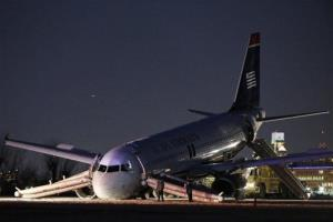 Investigators work near a damaged US Airways jet at the end of a runway at  Philadelphia International Airport yesterday.