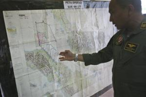 Lt. Col Bambang Sudewo examines a map following a search operation for the missing Malaysia Airlines Boeing 777 that was conducted over the Strait of Malacca, at Suwondo air base in Indonesia today.
