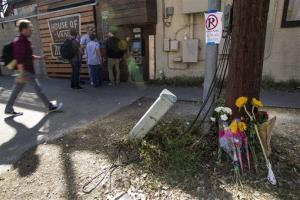 Flowers are placed against a utility pole near the scene.