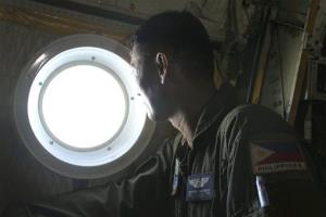 Philippine Air Force C-130 crew members search over the South China Sea for the missing Malaysian plane.