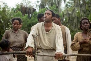 This image released by Fox Searchlight shows Chiwetel Ejiofor, center, in a scene from the film, 12 Years A Slave.