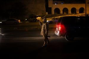 A Libyan army soldier checks vehicles at a checkpoint at a gate of Tripoli's main port in Libya, Sunday, Nov. 24, 2013.