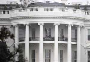 Law enforcement officers photograph a window at the White House in Washington, Wednesday, Nov. 16, 2011, as seen from the South Lawn.
