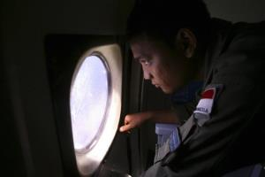 An Indonesian Navy crew member scans the water during a search for the plane.