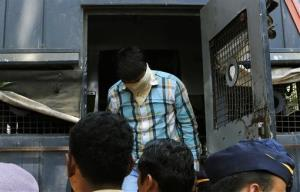 One of four men convicted of gang raping a photojournalist  in India's financial capital of Mumbai last year exits a police van as he is brought to prison, in Mumbai, India, Thursday, March 20, 2013.