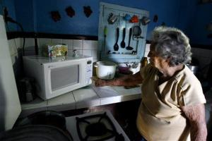 Ana Magdalena Melian, 91, uses her microwave oven in Las Guasimas,Cuba, Wednesday, March 26, 2008.