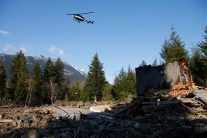 A helicopter flies low over the mudslide-affected area in Oso, Wash.