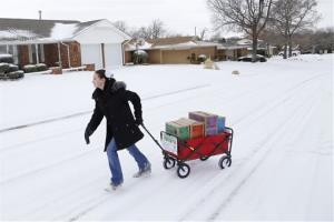 In this file photo from Feb. 6, 2014, Girl Scout Katie Francis pulls her wagon full of boxes of cookies in the snow through a neighborhood in Warr Acres selling cookies in Oklahoma City.