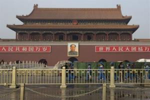 Cleaners walk past an area shielded by green nets in front of Tiananmen Gate following a car fire in Beijing, China, Monday, Oct. 28, 2013.