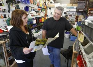 In this photo taken Tuesday, March 4, 2014, Heather Willis, manager of the Pioneer Mining Supply Co., goes over a map of areas open to gold panning with a prospective gold prospector.