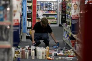 A man picks up fallen goods at a CVS store in La Mirada, Calif.