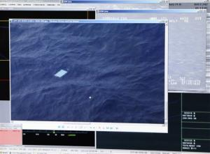A photo taken off a computer monitor onboard a New Zealand Air Force jet shows an object floating in an area within the search zone.