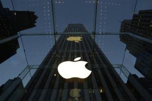 In this Wednesday, Nov. 20, 2013, file photo, the Apple logo is illuminated in the entrance to the Fifth Avenue Apple store, in New York.