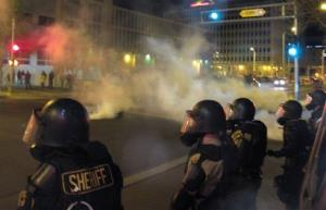 Riot police launch tear gas toward activists in downtown Albuquerque, NM, following a 10-hour protest around the city, Sunday, March 30, 2014.