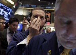 Trader Greg Mulligan, center, works on the floor of the New York Stock Exchange, Tuesday, March 25, 2014.
