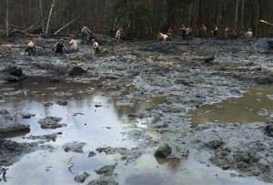 Washington Air National Guardsmen methodically make their way through the mud and wreckage left behind by Saturday's mudslide near Oso, Wash., Friday, March 28, 2014.