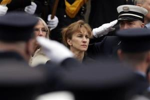 Firefighters salute as Kristen Walsh watches the casket of her late husband, Edward Walsh, is lifted onto Engine 33 in Watertown, Mass., Wednesday.