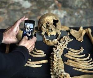 A member of the media photographs the skull of one of the skeletons found by construction workers under central London's Charterhouse Square. The skeleton appears to have belonged to a plague victim.