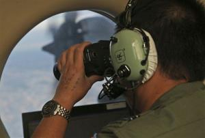 An Australian officer uses binoculars onboard a Royal Australian Air Force plane during the search.