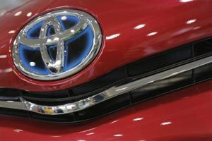 In this Aug. 2, 2013 file photo, the emblem of a Toyota car shines at Toyota Motor Corp.'s showroom in Tokyo.