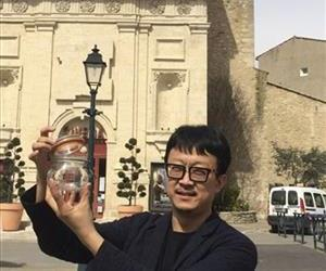 In this photo taken on March 29, 2014, Beijing artist Liang Kegang collects fresh air in the commune of Forcalquier in Provence, France.