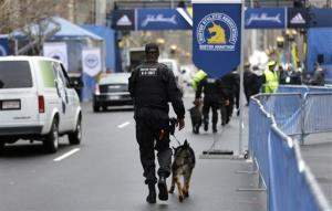 A law enforcement official patrols the area with a dog near the finish line of the Boston Marathon Tuesday in Boston. The race runs next Monday.