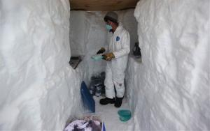 In this July 15, 2011 photo, in a trench dug into the 2-mile-thick Greenland Ice Sheet, a researcher preserves ice samples at Summit Station.