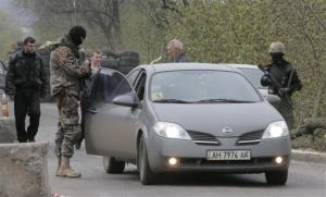Pro-Russian gunmen control a road after a night fight at the check point which is under the control of pro-Russian activists in the village of Bulbasika, Ukraine, Sunday, April 20, 2014.