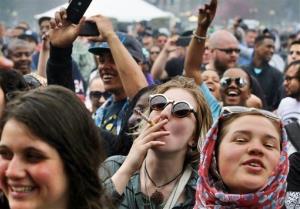 With the Colorado state capitol in the background, partygoers dance to live music and smoke pot on the first of two days at the 4/20 festival in Denver, Saturday, April 19, 2014.