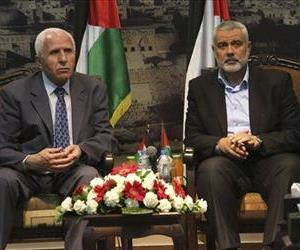 Gaza's Hamas Prime Minister Ismail Haniyeh, right, and senior Fatah official Azzam al-Ahmad meet in Gaza for reconciliation talks between the rival Palestinian groups, April 22, 2014.