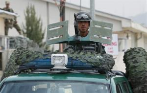 An Afghan policeman stands guard in his vehicle in front of the main gate of Cure International Hospital in Kabul, Afghanistan, Thursday, April 24, 2014.