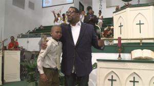 In an April 10, 2014, image provided by WXIA-TV, Willie Myrick is embraced by Grammy Award-winning gospel singer Hezekiah Walker in front of the congregation at Mt. Carmel Baptist Church in Atlanta.