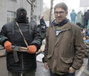 In this photo taken on Sunday, April 13, 2014, a reporter Simon Ostrovsky, right, stands next to a Pro-Russian gunman at a seized police station in the eastern Ukraine town of Slovyansk.