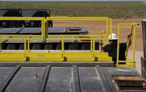 A worker looks over tanks holding waste water from hydraulic fracturing Sept. 24, 2013, in Midland, Texas.