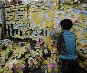 A man attaches messages for the missing students on a wall at Danwon High School in Ansan, South Korea.