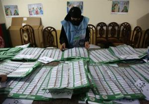 In this Saturday, April 5, 2014, file photo, an Afghan election worker counts ballots at a polling station in Jalalabad, east of Kabul, Afghanistan.