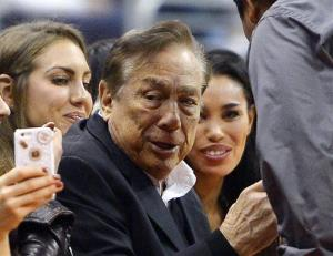 In this photo taken on Friday, Oct. 25, 2013, LA Clippers owner Donald Sterling and V. Stiviano watch the Clippers play in Los Angeles.